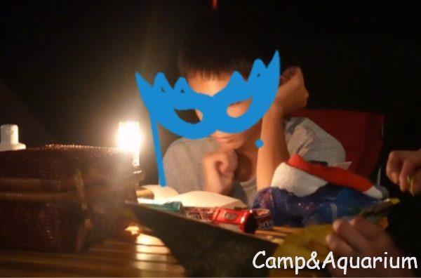 夜のキャンプ場でリトルランプ ノクターンの灯りで読書する息子